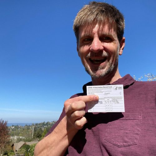 Rob F., holding his COVID-19 vaccination record card