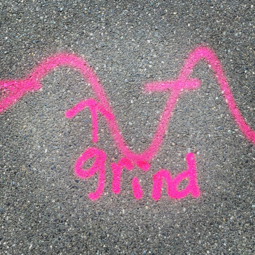 """the word """"grind"""" spray-painted onto some pavement along with a wavy line"""